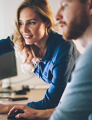Woman teaching man something on computer